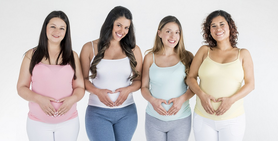 Loving group of pregnant women making a heart shape with their hands on their belly